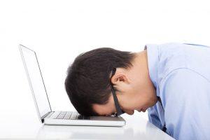 man met hoofd op laptop